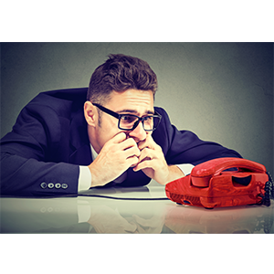 Man sits nervously looking at red phone awaiting phone interview for a job.